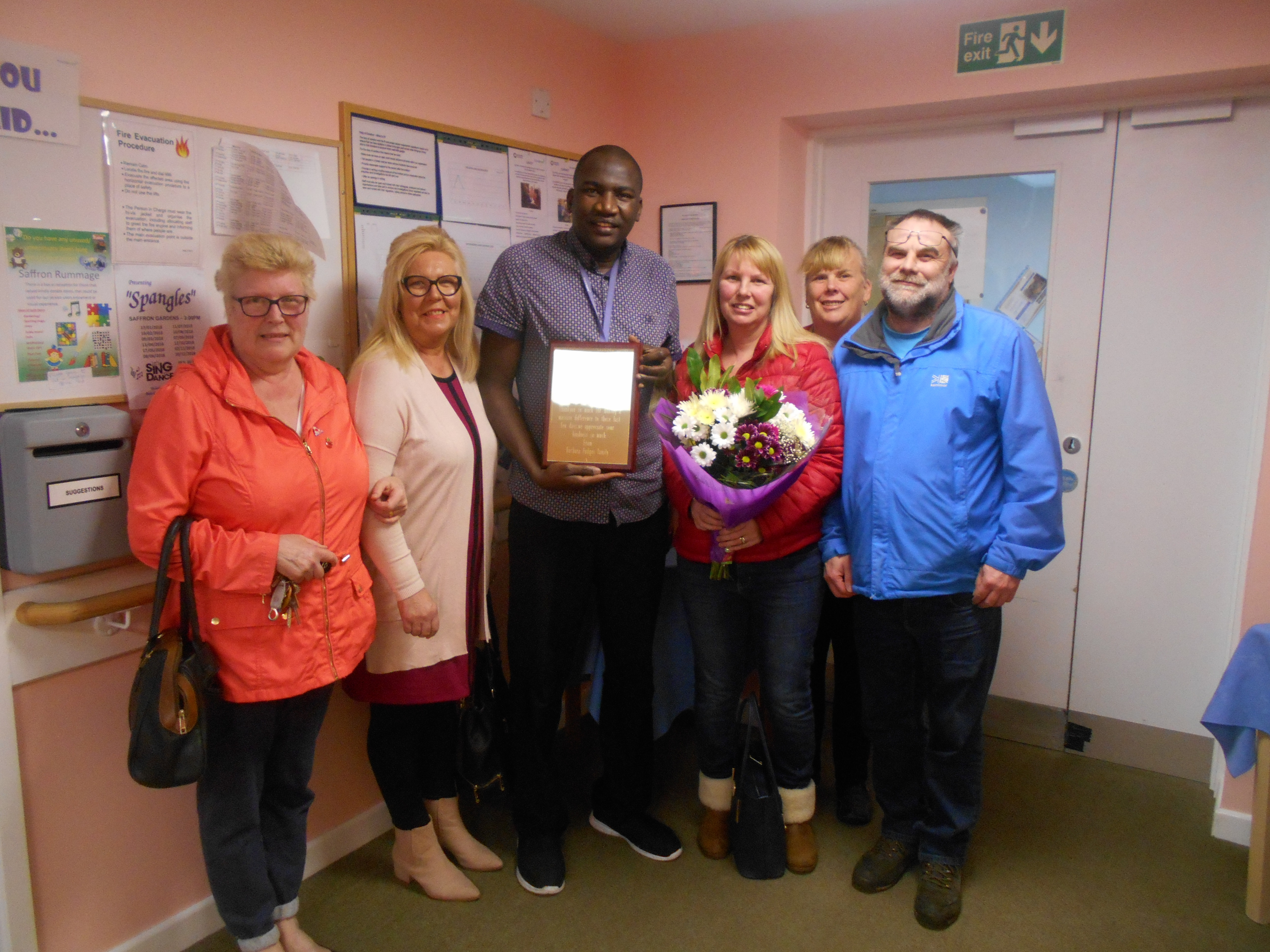 Julie Billitteri and her family present thank you plaque to Buba Touray, for end of life care